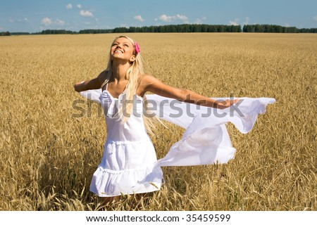 Photo of happy female with white fabric in wheat meadow - stock photo