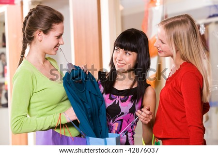 Photo of happy girl showing fashionable blouse to her friends - stock photo