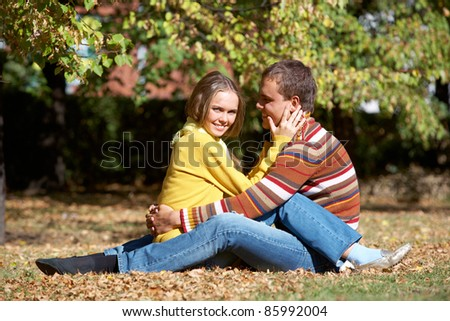 Photo of happy girl with handsome male sitting on ground in autumn - stock photo