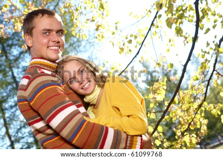 Photo of happy girl with handsome male spending time in autumnal park - stock photo