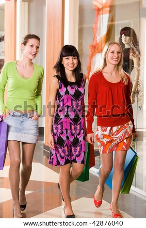 Photo of happy girls walking down trade center during shopping - stock photo