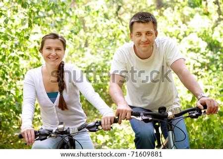 Photo of happy husband and wife riding bicycles outdoors - stock photo