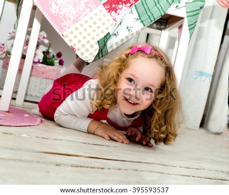 photo of happy little girl on the floor under the table - stock photo