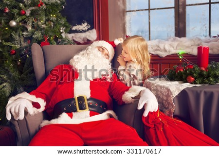 Photo of happy littlle smiling girl looking at sleeping Santa Claus with big bag of presents  - stock photo