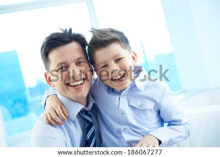 Photo of happy man and his son embracing and looking at camera - stock photo