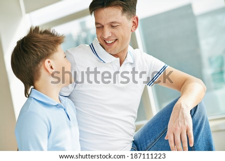 Photo of happy man and his son looking at one another while talking - stock photo