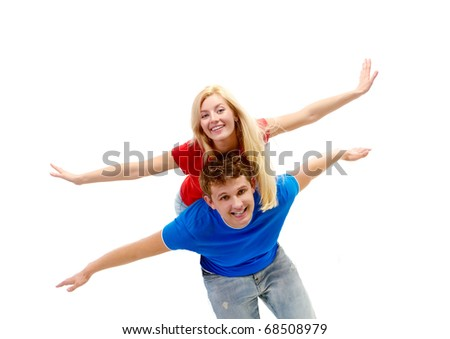 Photo of happy man giving piggyback to his girlfriend while both looking at camera - stock photo