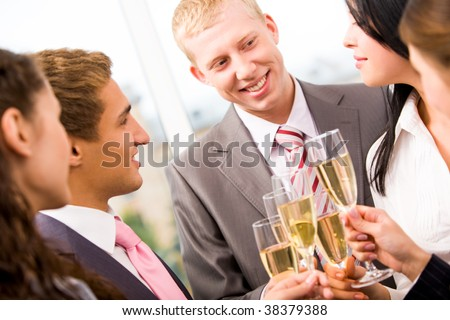 Photo of happy man holding flute with champagne and smiling at colleagues during party - stock photo