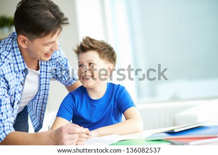Photo of happy man looking at his son while talking to him at home - stock photo