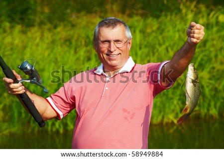 Photo of happy mature man showing carp caught by him - stock photo
