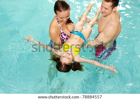 Photo of happy parents teaching their daughter how to swim - stock photo