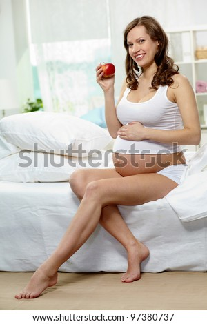 Photo of happy pregnant woman holding ripe apple - stock photo