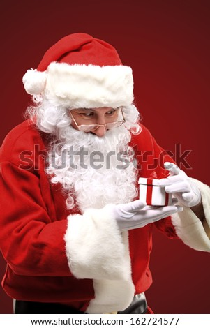 Photo of happy Santa Claus looking into white giftbox in isolation - stock photo