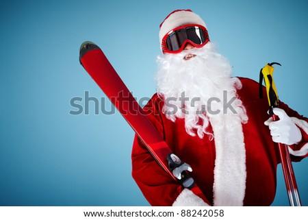 Photo of happy Santa Claus with skis looking at camera - stock photo