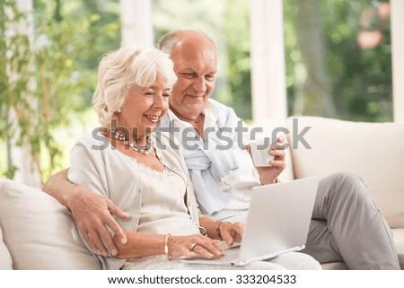 Photo of happy senior pair with computer skills - stock photo