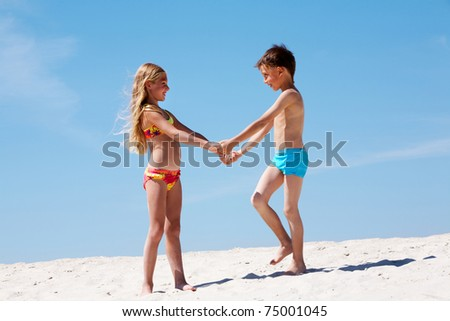 Photo of happy siblings on sand having nice summer vacation - stock photo
