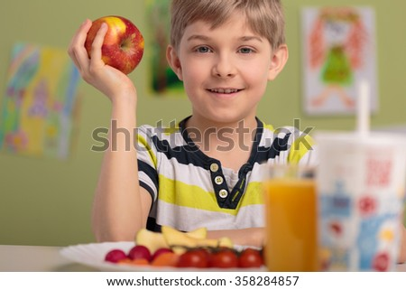 Photo of healthy kid holding tasty red apple - stock photo