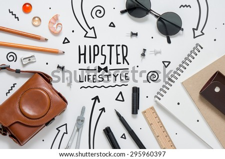 Photo of hipster workplace with lots of stationery objects and glasses. Studio shot on light background with arrow. - stock photo