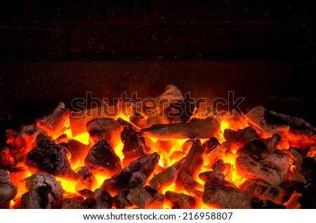Photo of hot sparking live-coals burning in a barbecue  - stock photo