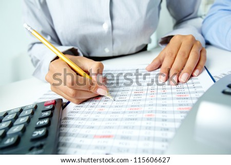 Photo of human hands holding pencil and marking numbers in documents - stock photo