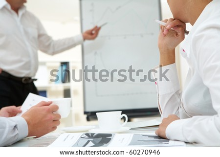 Photo of human hands over workplace on background of teacher by the whiteboard - stock photo