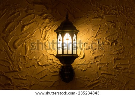 Photo of included sconces on textured dark yellow wall. - stock photo