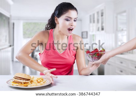 Photo of Indian woman taking healthy strawberry and refuse unhealthy hamburger in the kitchen - stock photo