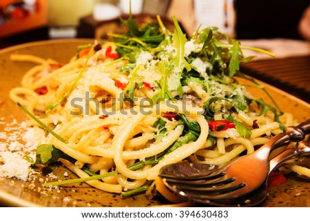 photo of Italian Pasta spaghetti with meat, red pepper, Parmesan cheese and arugula leaves - stock photo