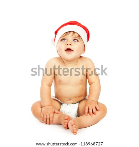 Photo of little baby boy wearing Santa Claus hat, small cute child sitting in diaper isolated on white background, lovely infant celebrate Christmas eve, New Year holiday, happiness concept - stock photo