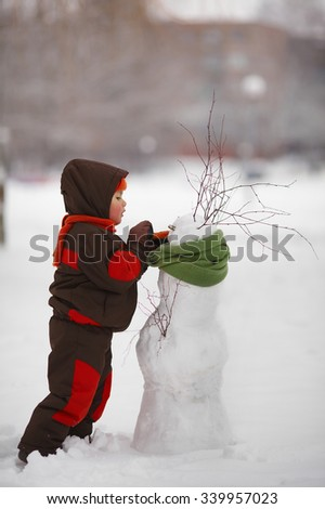 photo of little cute boy with snowman - stock photo