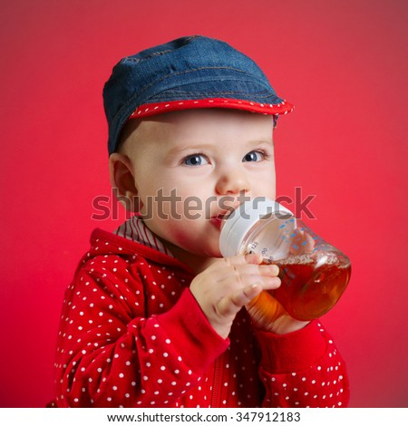 photo of little girl drinking juice from bottle - stock photo