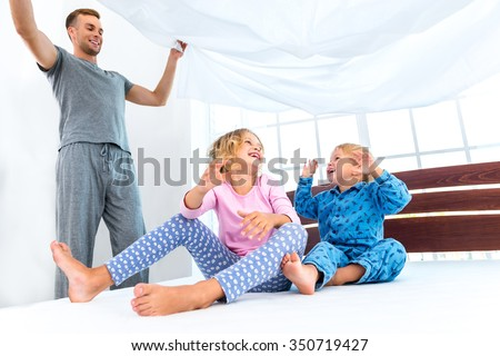 Photo of loving family making bed. Young family demonstrating quality of mattress and holding blanket - stock photo