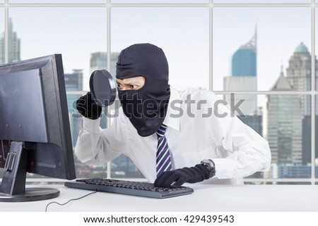 Photo of male hacker wearing mask and using magnifier to steal information on the computer in the office - stock photo