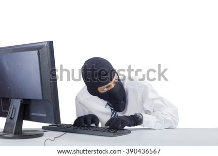 Photo of male robber wearing mask while hacking a computer to steal information, isolated on white background - stock photo