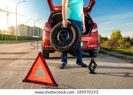 Photo of man holding spare wheel against broken car - stock photo