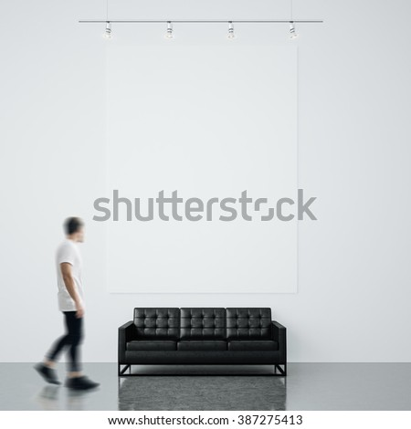 Photo of man in gallery. Waching empty canvas hanging on the brick wall and black generic design sofa concrete floor. Square Blank mockup. Motion blur - stock photo