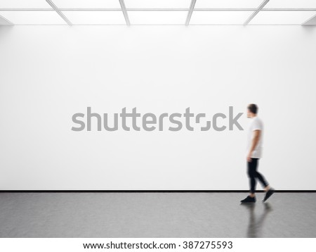 Photo of man in modern gallery looking at the empty canvas. Blank mockup, motion blur  - stock photo