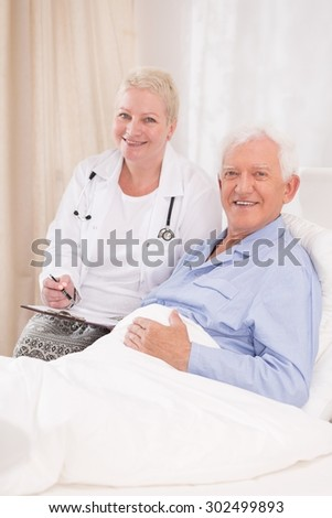 Photo of mature caring doctor and her elderly patient - stock photo