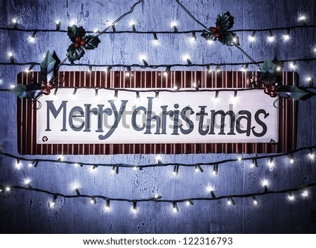 Photo of Merry Christmas banner on blue grunge door at home, happy New Year, glowing electrical garland, Christmastime house interior, congratulations postcard, holiday illumination - stock photo