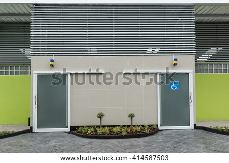Photo of modern toilet for disabled people.  - Outdoor public toilet  with sign for disabled people. - stock photo