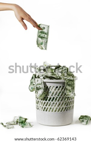 Photo of money is in a trash bucket over hand with dollar - stock photo
