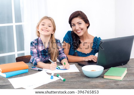Photo of mother and little daughter. Nice white interior with wooden table. Mother using laptop while her daughter drawing. They looking at camera and smiling - stock photo