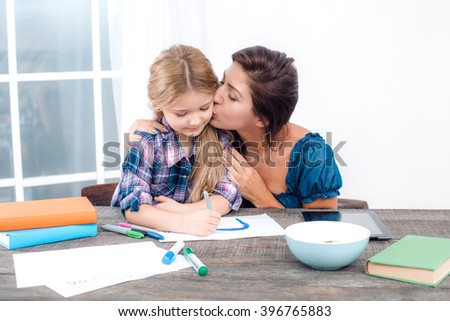 Photo of mother and little daughter using tablet computer. Nice white interior with wooden table. Mother kissing her daughter - stock photo