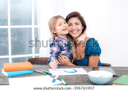 Photo of mother and little daughter using tablet computer. Nice white interior with wooden table. Daughter and mother hugging - stock photo