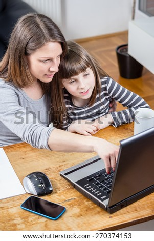 Photo of mother pointing at laptop with daughter - stock photo