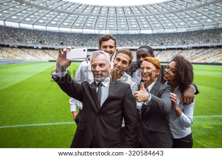 Photo of multi ethnic business group. Mixed race business team making photo on mobile phone. Business people standing on modern sport track. Accent on leader of group. Stadium as a background - stock photo