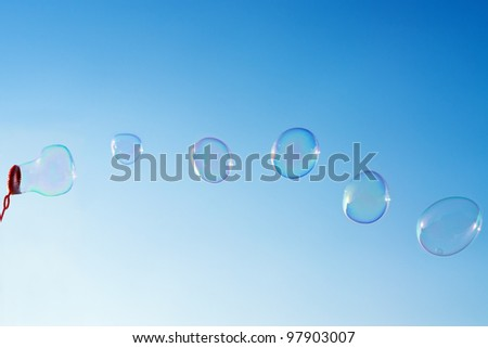 Photo of natural shaped soap bubbles over clear blue sky - stock photo