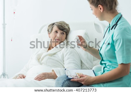 Photo of nurse giving medicines to old patient - stock photo