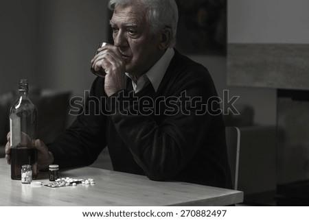 Photo of older sad man drinking alcohol alone - stock photo