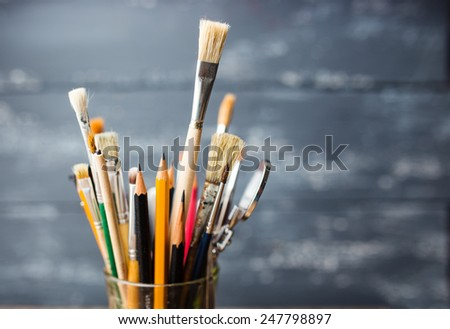 Photo of paint brushes in a glass standing on old wooden table, small dof - stock photo
